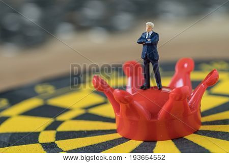Miniature people brave confident figure businessman standing on crown at the center of dartboard as business goal achievement concept.