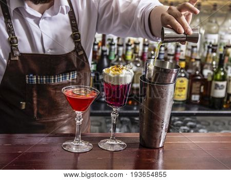 close up of bartender is adding ingredient in shaker at bar counter