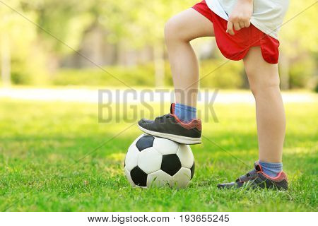 Legs of little boy with soccer ball in green park on sunny day