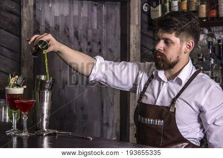 brutal bartender making alcohol coctail in restaurant