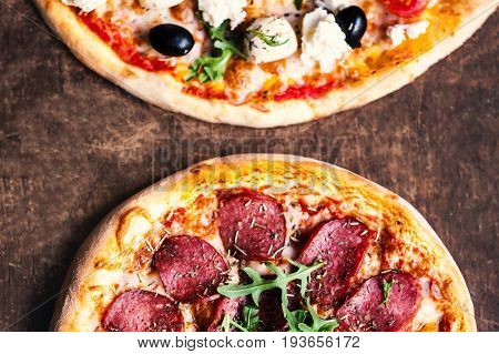 Hot pizzas slice with salami olives and cheese on a rustic wooden table. Top view. Fresh Pizza on dark background with Copy space.
