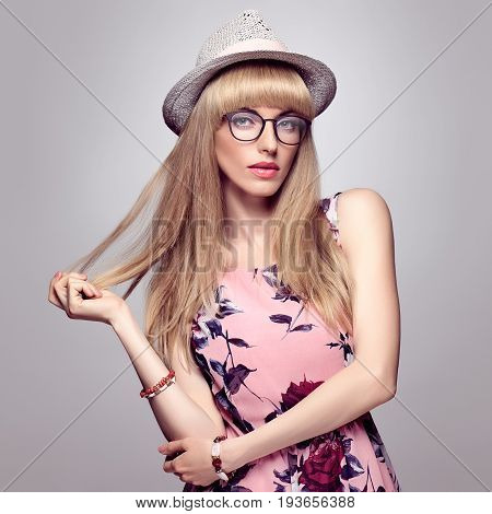 Fashion Beauty Sensual Blond Girl in Stylish glasses, Summer Outfit. Shiny Straight hair, fashion Makeup, Blue Eyes. Trendy Bang Hairstyle. Glamour Romantic Model in Floral Dress, fashion summer Hat
