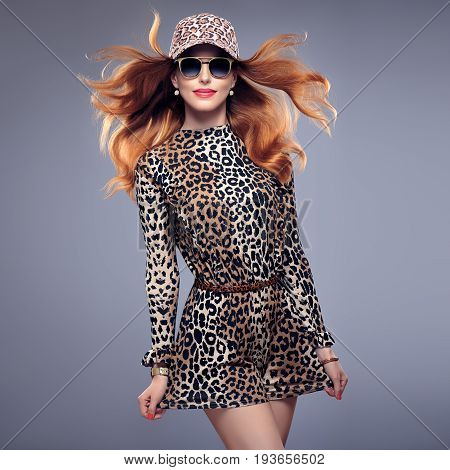 Fashion Redhead Model Girl in Sexy Summer Leopard Outfit. Stylish Wavy hairstyle, fashion Sunglasses, Beauty Woman in Trendy Summer Jumpsuit, Glamour Cap. Playful Luxury Girl in fashion pose