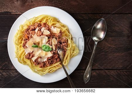 An overhead photo of a plate pf bolognese pasta with grated parmesan cheese and fresh basil leaves, with a fork and a spoon, on a dark rustic texture with a place for text