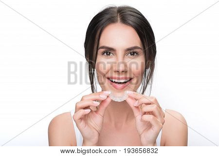 I want to adjust my teeth. Portrait of joyful girl wearing transparent orthodontic device for improving bite. She is standing and looking at camera with excitement. Isolated