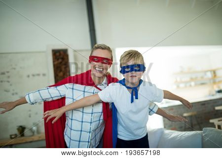 Mother and son pretending to be superhero in living room at home
