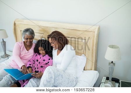Smiling family watching photo album together in living room at home