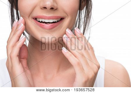 Close up of chin of young woman touching her skin with admiration. She is smiling. Isolated