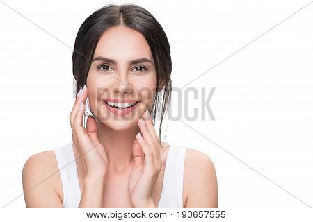 Portrait of happy brunette girl enjoying purity of her face by hands. She is looking at camera and smiling. Isolated and copy space