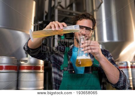 Portrait of smiling worker pouring beer in beaker at factory