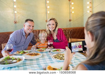 Girl photographing family through smart phone at restaurant