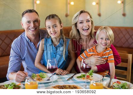 Portrait of cheerful family sitting at restaurant