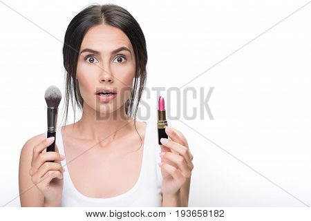 Puzzled young woman is choosing between two cosmetic products. She is holding brush with powder and bright lipstick. Isolated and copy space