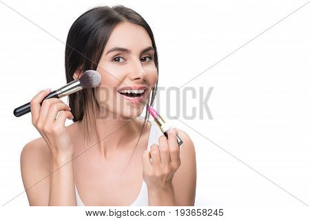 Joyful young woman is applying powder on her cheek by brush and lipstick on lips. She is standing and looking at camera with happy smile. Isolated and copy space