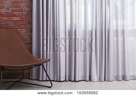 Chair and room window with grey curtains