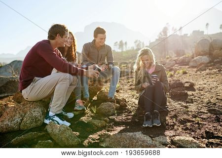 Smiling group of young friends sitting on rocks talking together and enjoying coffee at their campsite in the early morning