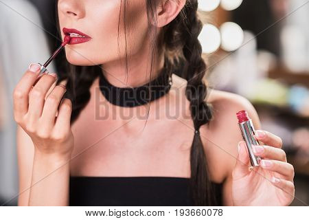Close up of sensual young woman applying red lip gloss elegantly