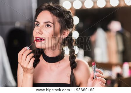 Dreamful brunette girl is doing make-up by red lipstick in dressing room. Mirror with light bulbs on background. Portrait