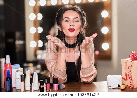 Attractive young woman is sending air kiss to camera with love. She is sitting at table backstage near different cosmetic items. Portrait
