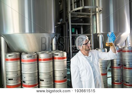 Scientist examining beer in beaker at warehouse