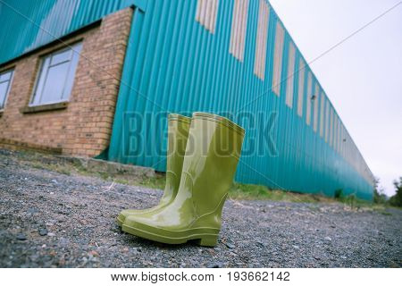 Pair of green wellington boot on dirt track