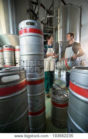 Coworkers discussing while standing by vats and kegs at warehouse