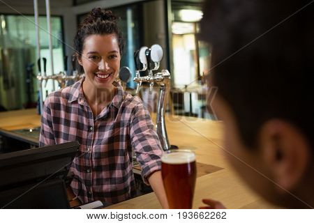 Smiling barmaid serving drink to male customer at bar counter
