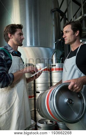 Coworkers discussing while examining kegs at warehouse