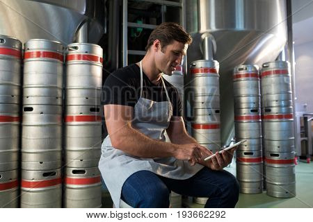 Worker using digital tablet while sitting on keg at warehouse