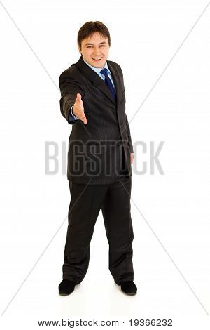 Full length portrait of smiling businessman stretches out hand for handshake isolated on white