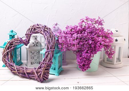 Decorative heart lilac flowers and brigh lanterns on white wooden background. Selective focus. Still life.