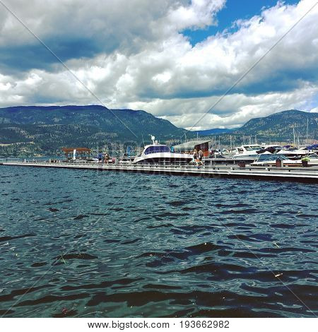 High water at marina with boats docked and people walking on pier. Debris in water. Kelowna BC Canada.