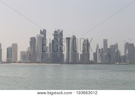 DOHA, QATAR - JULY 3, 2017: Doha's towers, seen across the humid Gulf waters as the Saudi ultimatum expired
