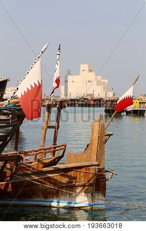 DOHA, QATAR - JULY 3, 2017: Qatari flags flutter from traditional wooden dhows in front of the Museum of Islamic Art in Doha, on the day that the Saudi ultimatum in the Gulf Crisis expired