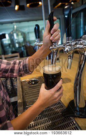 Cropped hands of barmaid pouring drink from tap in glass at counter in restaurant