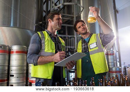 Coworkers examining beer in beaker at warehouse