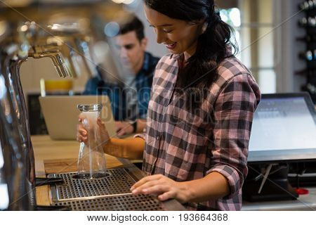 Barmaid preparing drink with male customer using laptop in background at restaurant
