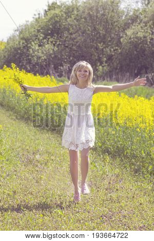 Girl with bouquet of rape flowers walking on country road