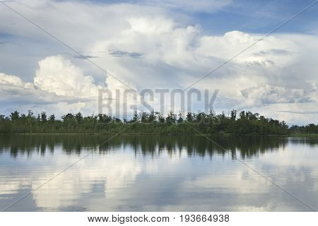 A calm Minnesota lake with pine trees below dramatic clouds