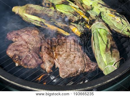 Two rib eye steaks and ears of sweet corn in the husks cook on a smokey charcoal grill.
