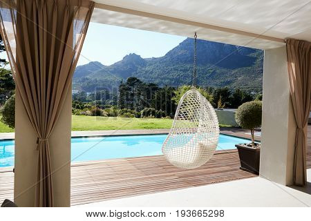 Suspended Seat Next To Decking Around Outdoor Swimming Pool