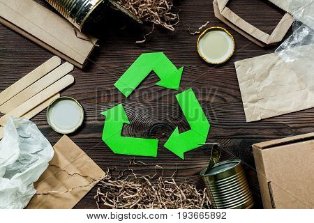 Garbage for recycling with recycling symbol on wooden background top view.