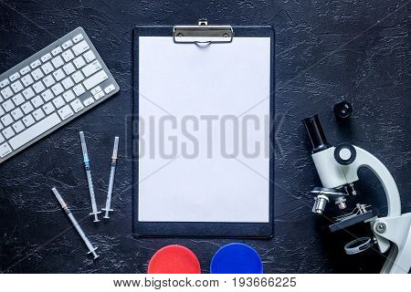 Heathcare concept. Medical tests. Microscope, syringe, Petri dish on grey stone background top view.