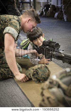 Ship Tour USS Kearsarge (LHD 3) Wasp-class amphibious assault ship: US Navy personnel helps unidentified boy take aim through rifle scope on M240B medium machine gun. Fleet Week NEW YORK MAY 25 2017.