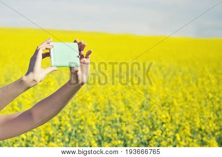 Technology summer holidays vacation and people concept - hands of woman taking photo or selfie by smartphone on rape field