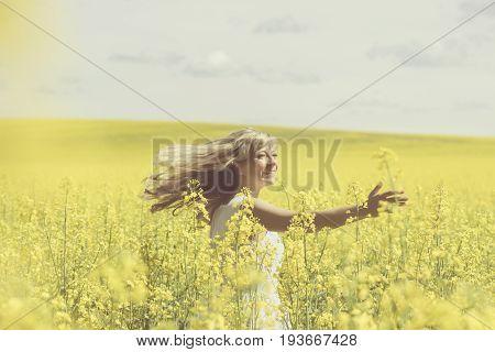 Sun shines through woman's blonde hair while she whirls on rape field