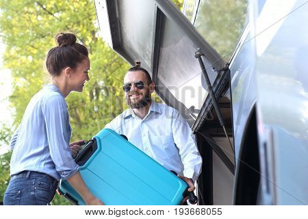 The passenger inserts the suitcase into the luggage compartment on the bus.