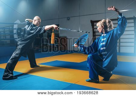 Wushu fighters, man with sword and woman with fan