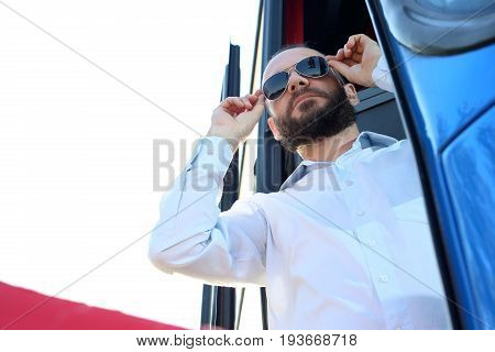 The bus driver improves sunglasses. Coach driver in the bus