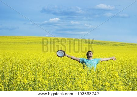 Young happy man standing on a meadow with raising hands and looking to a sky